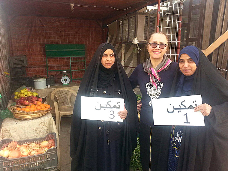 Hala Sarraf (of IHAO) stands with two displaced women who are recent recipients of small business start-up funds.