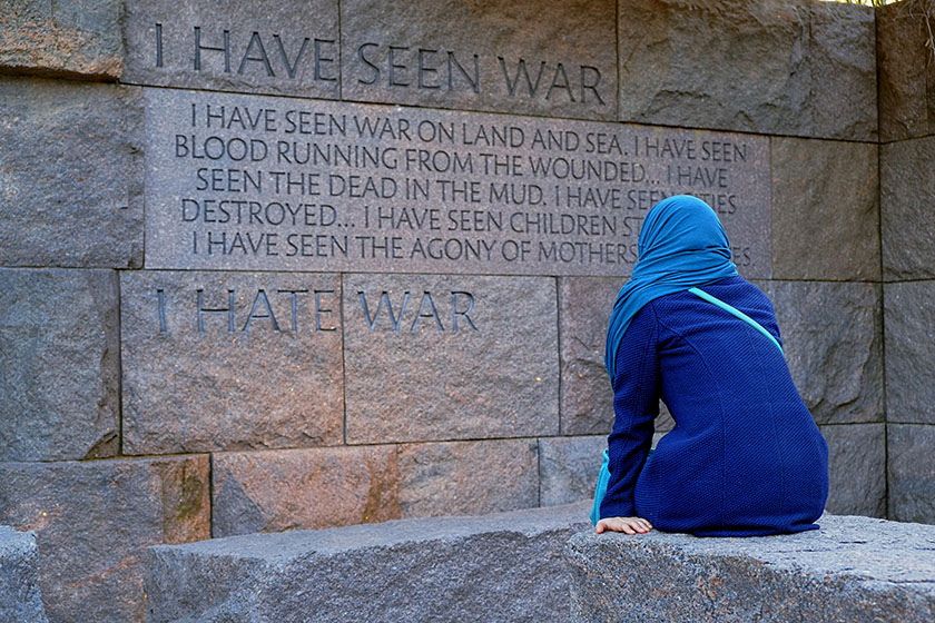 "A woman in a head scarf pauses in front of a quote at the Franklin Delano Roosevelt Memorial. ""I have seen war. I hate war."""