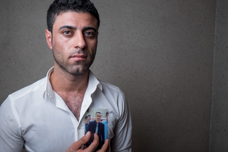 A picture of Sinan holding a photo of his friend recently killed by ISIS