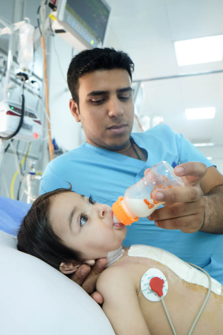Baby Adam being fed by Ali, an ICU nurse