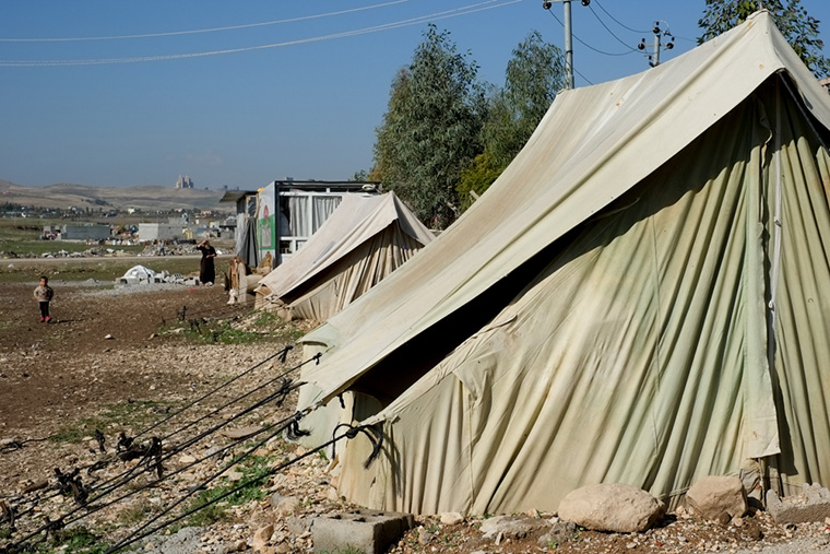 Tents and shipping containers, now home to displaced Iraqi families, line a boundary fence.