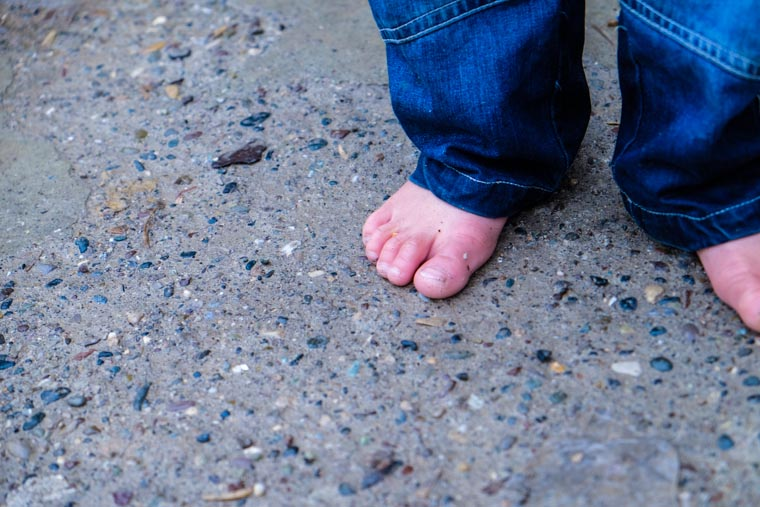 A child in bare feet, standing on cold concrete, before our partners delivered warm boots.