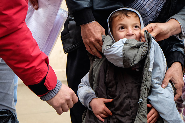 A displaced Shabak dad tries a coat on his son, determined to find one that fit just right.