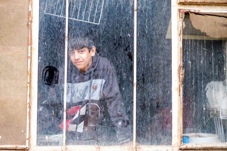 Boy looking through window of one of the old classrooms/where his family lives.