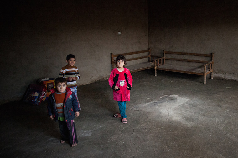 Three displaced children in Baghdad stand in their temporary home. The space is dark and empty, the concrete walls and floor bare.