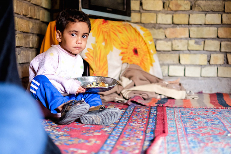 A young displaced Iraqi boy eats his lunch in a temporary home.