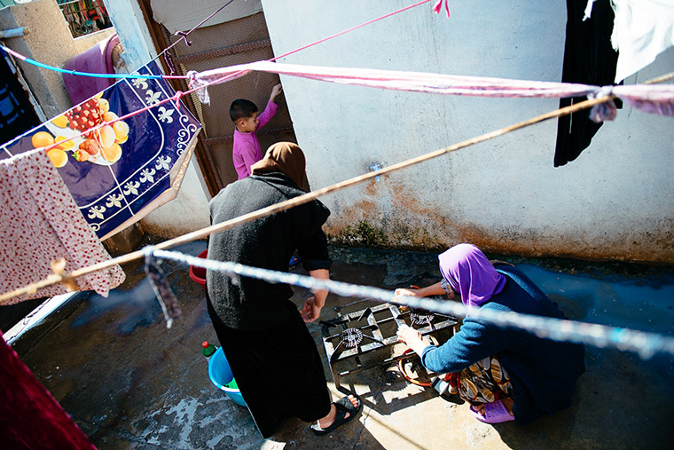 Displaced families cook outside their temporary home—an elementary school, in Iraq.