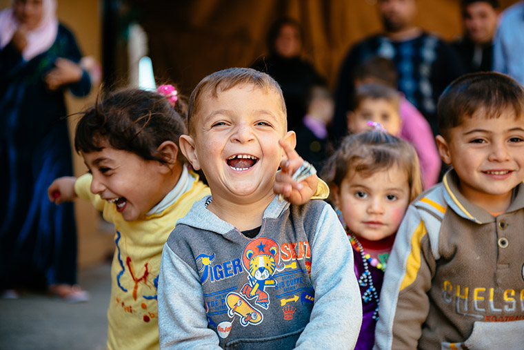 A displaced child in Iraq, a Shabak, laughing