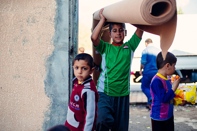 Boys help to carry rolls of carpet. They are able to help because, displaced by war, they are now out of school.