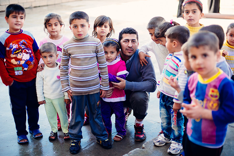 A group of displaced children stop playing just long enough to pose for a photo. Even though it is mid-morning on a school day, they aren't in school.