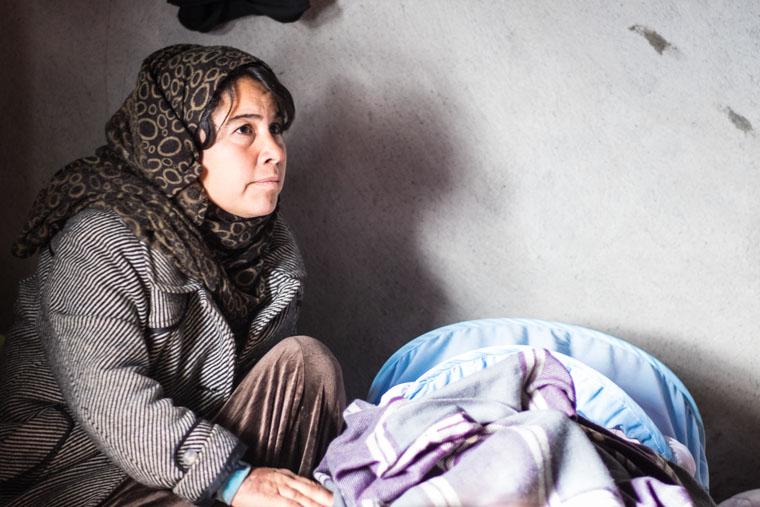 Sozan, a displaced Yezidi in Kurdistan, kneels beside her new baby.