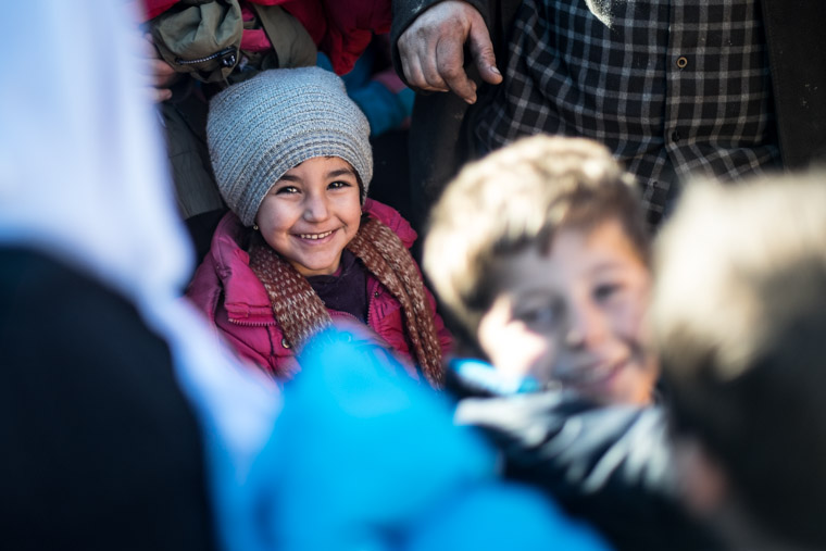 A displaced Yazidi girl smiling in her new coat