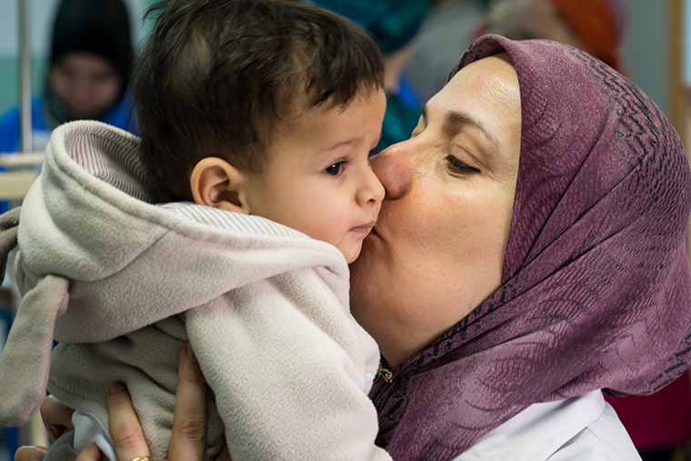 Dr. Naima kisses a small boy, who has come to the hospital in Libya to have his congenital heart defect fixed.