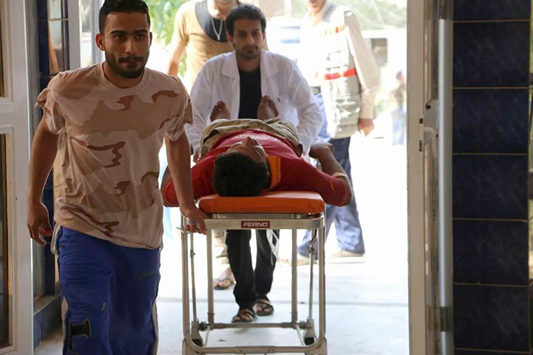 Dr. Mohammed wheels a wounded farmer into the hospital.