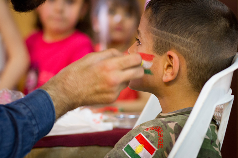 A young boy dressed in military fatigues gets the Kurdish flag painted on his face during an Easter party hosted by a local Assyrian church.
