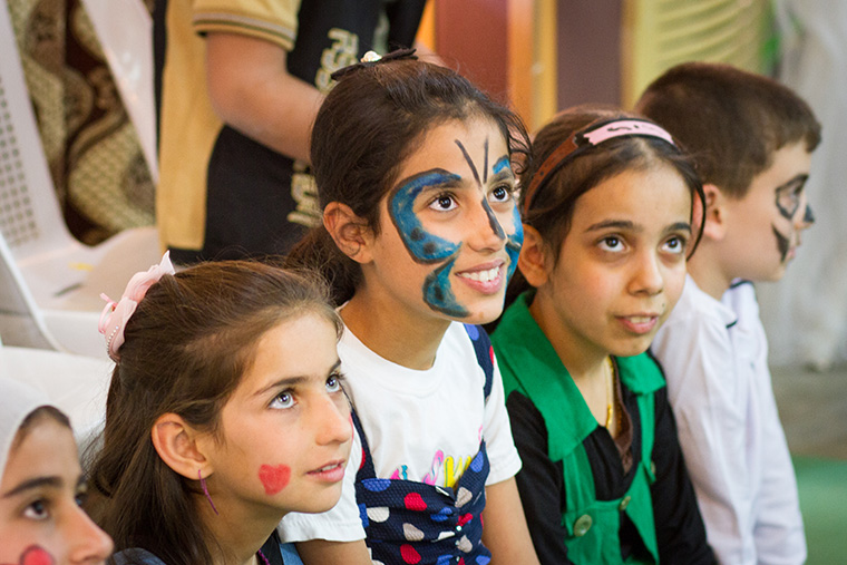 Children, their faces brightly decorated with face paint, participate in a game at an Easter party hosted by a local Assyrian church.