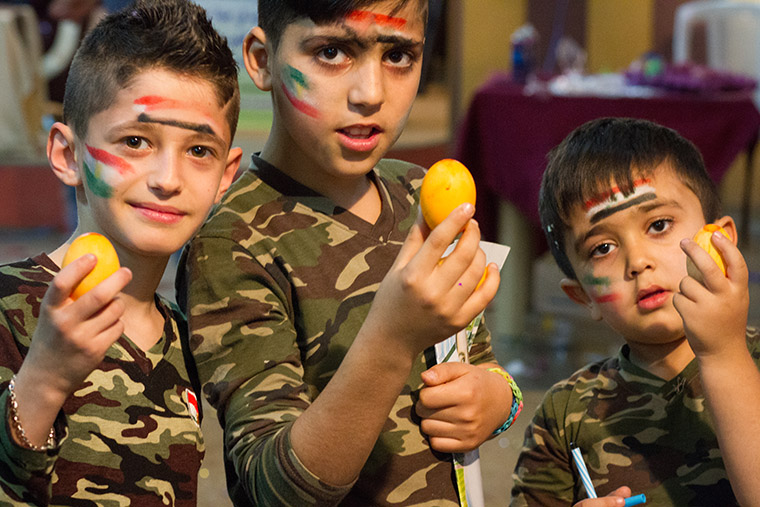 Three boys take a minute to pose for a photo at a recent Easter party, hosted by a local Assyrian church. The boys, dressed in military fatigues and adorned with flag face paintings, hold coloured eggs.