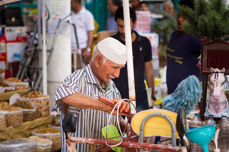 A vendor with a thin, white moustache prepares his wares.