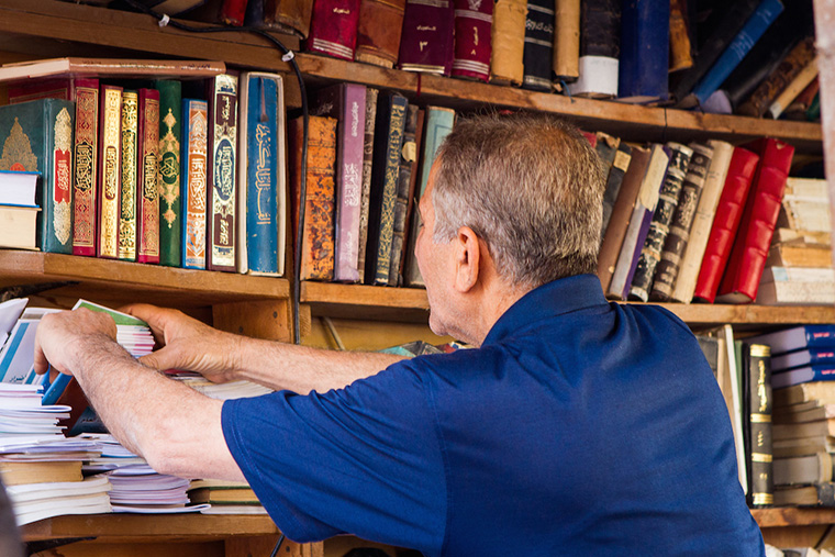 A vendor helps to find just the right book for a customer.