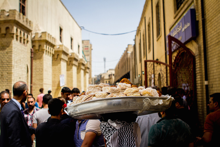 A tray of pastries is carried above the crowds in Baghdad's Mutanabi Street.