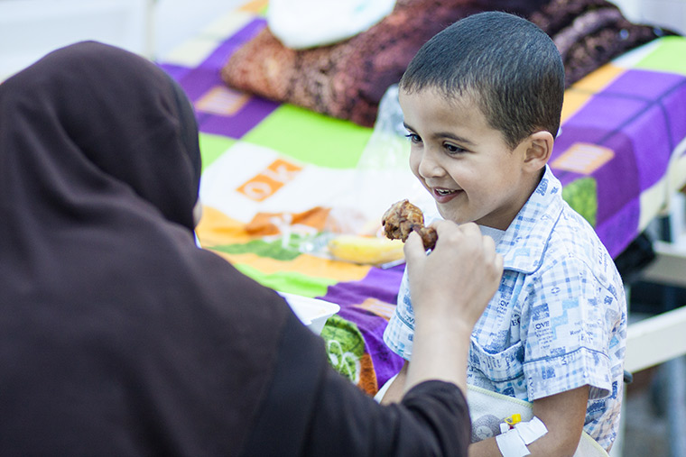 Hamam's mom helps him eat his first meal after his heart surgery: spaghetti, chicken and salad.