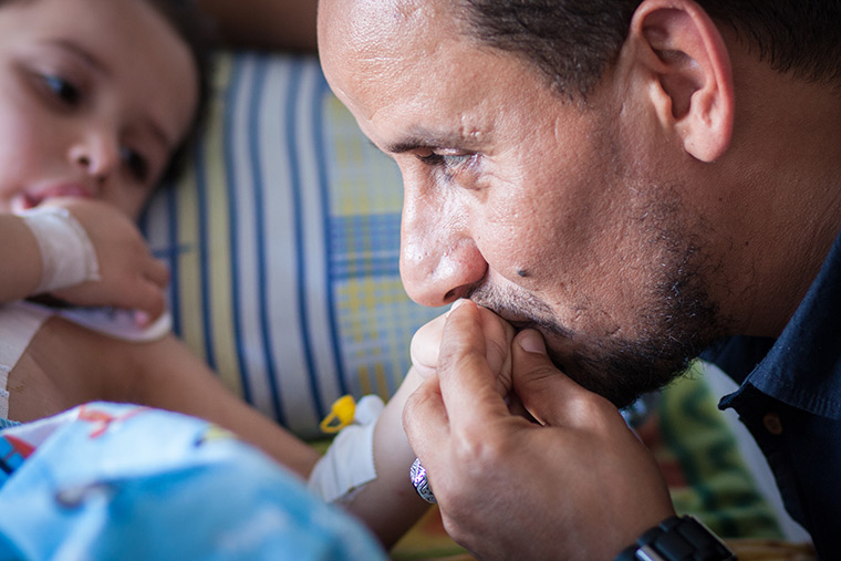 Walla's dad kisses her hand as she lays in bed and sucks her thumb after her lifesaving heart surgery.
