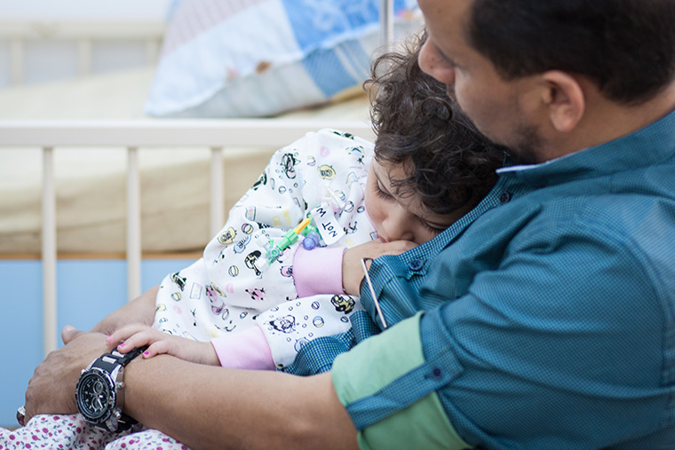 Walla's dad snuggles with her as she rests following her lifesaving heart surgery.