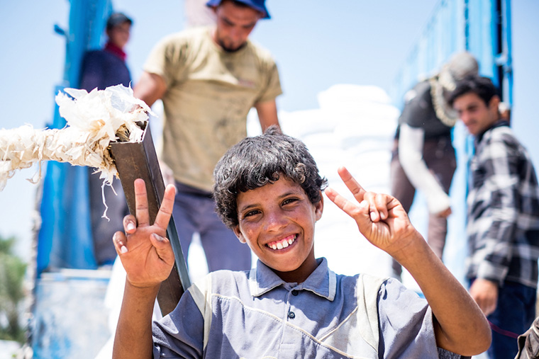 A young teenager stops to pose for a picture. He works long hours hauling a cargo cart, in the Iraqi heat, for little pay.