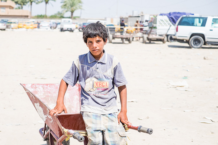Not so much a teenager anymore–more a man–he works in the heat hauling supplies to displaced families from Ramadi with his wheelbarrow.