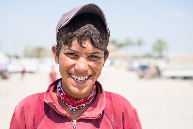This young man is already the breadwinner for his family. It's hard work, hauling supplies in +120 degree heat.