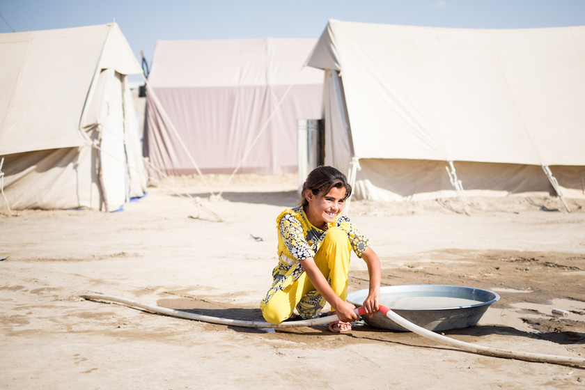 Refugee girl with water in Iraq camp