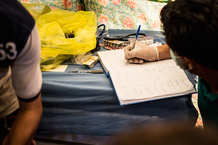 Dr. Nasir keeps a record of conditions found in displaced camp residents, as he assesses their conditions.