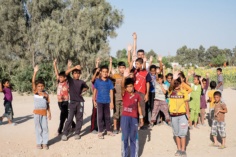 A crowd of displaced kids head off to play soccer with a ball that Emad pulled out of his supplies.