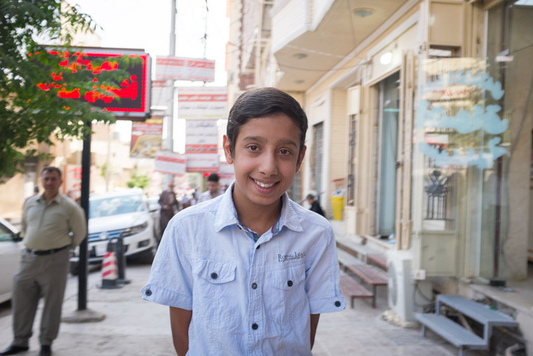 Ali stands outside the doctor's office, looking good after his heart surgery and two thumbs up from the doctor.