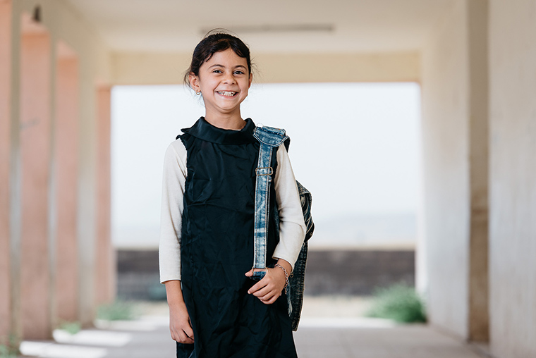 A young Iraqi girl poses in a hallway at her school. She is dressed in a uniform, backpack, and a big smile.