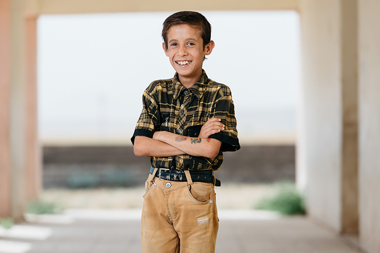When looking at this cute boy, displaced by ISIS and standing confidently with temporary tattoos applied to one arm, it's shattering to think about the plans ISIS has for boys just like him.