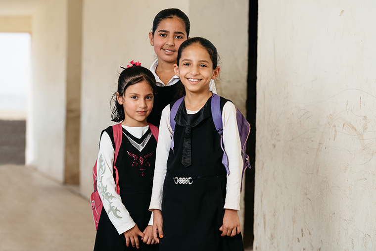 Three Iraqi girls wear school uniforms and backpacks...they are excited to go to school!