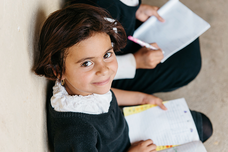 A young girl looks up from her school book and smiles.
