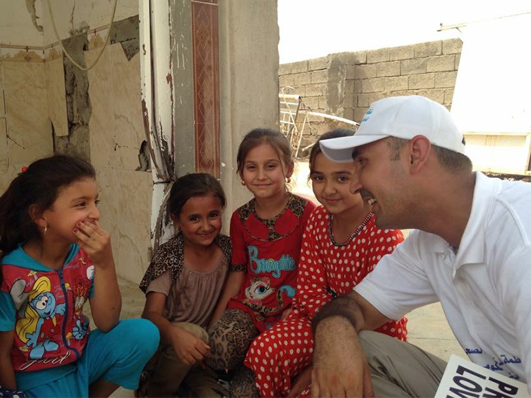 Ahmed takes time out from delivering relief aid in Iraq to talk to some giggly girls.