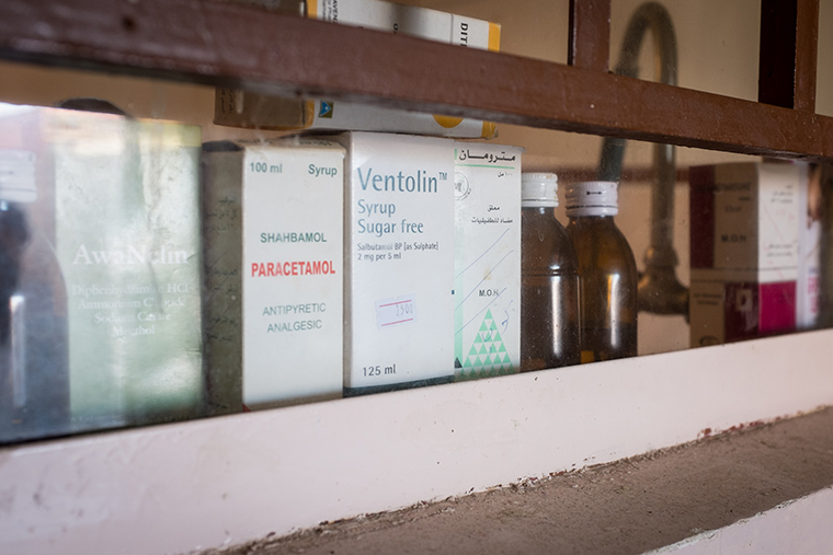 A row of cough syrup and medicine lines a window sill in an IDP house.