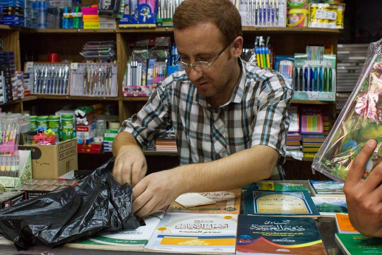 In a stationary store in the bazaar, choosing pencils and pens for back-to-school.