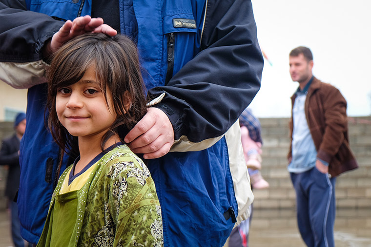 A displaced Iraqi girl waits her turn to get a coat.