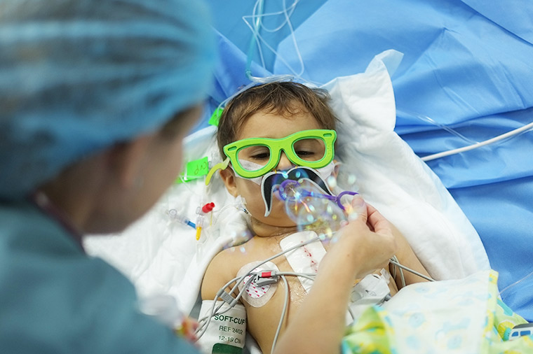 A nurse helps a young patient blow bubbles. He lays in his hospital bed, wired to machines, yet wearing large green foam glasses, just for fun.