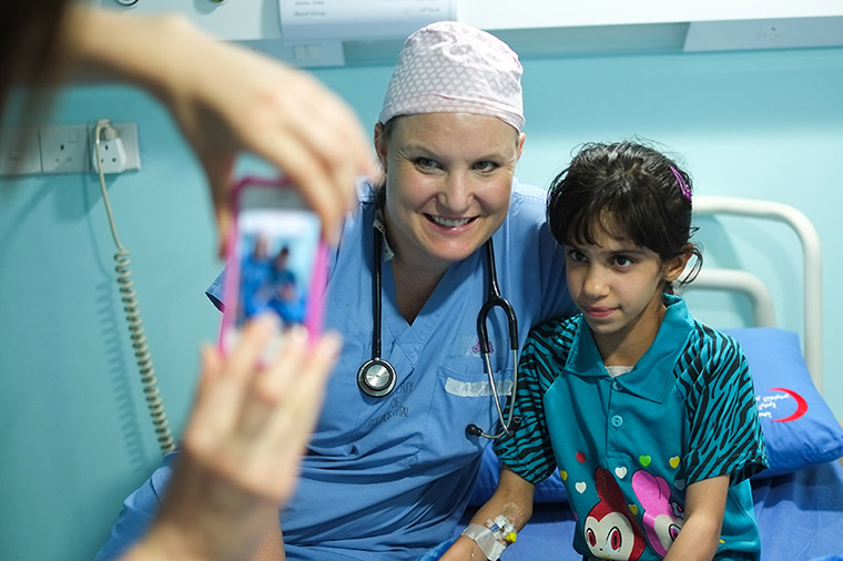 A nurse spends time with her patient, taking a photo with her to remember the moment.