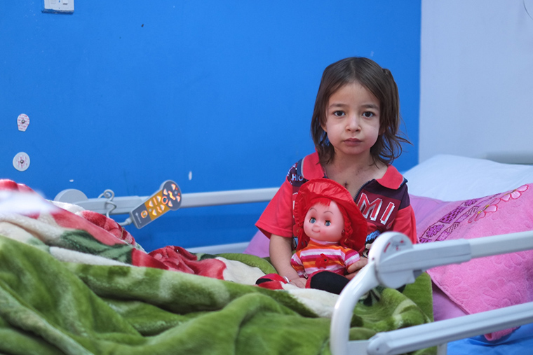 A young girl, Fatima, sits on her hospital bed in the city of Nasiriyah, Iraq.