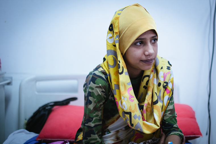 Saaja, sitting on her hospital bed, has been waiting 14 years for lifesaving heart surgery.