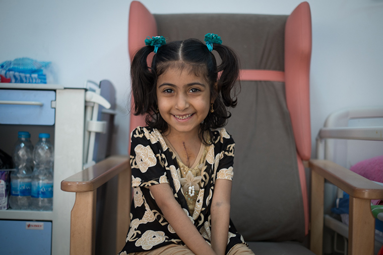 A young girl smiles, a beautiful scar across her chest, after her recent lifesaving heart surgery.