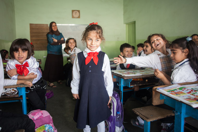 Deeya stands in her classroom, dressed in her navy uniform, surrounded by enthusiastic classmates.