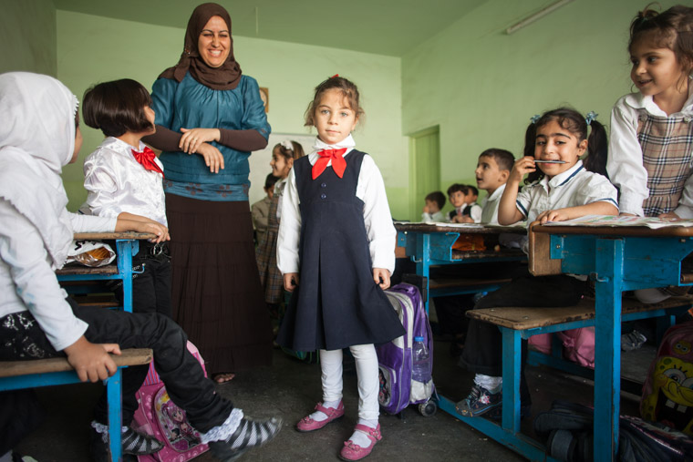 Deeya's teacher stands behind her, her backpack is beside her, and Deeya looks like any other student—as it should be!