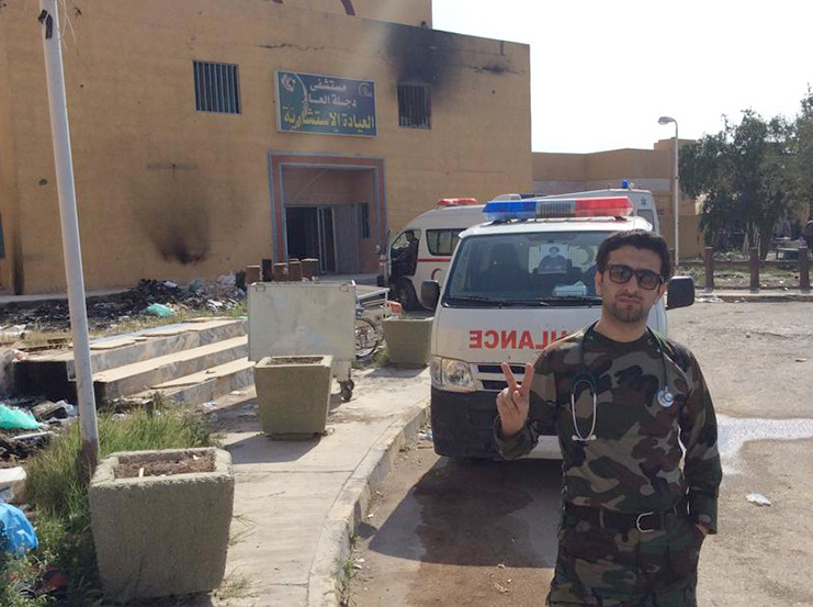 Dr. Mohammed standing in front of the hospital in Al Awja, previously controlled and burned out by ISIS.